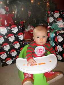 Starting to sit up in the Bumbo chair in front of the tree